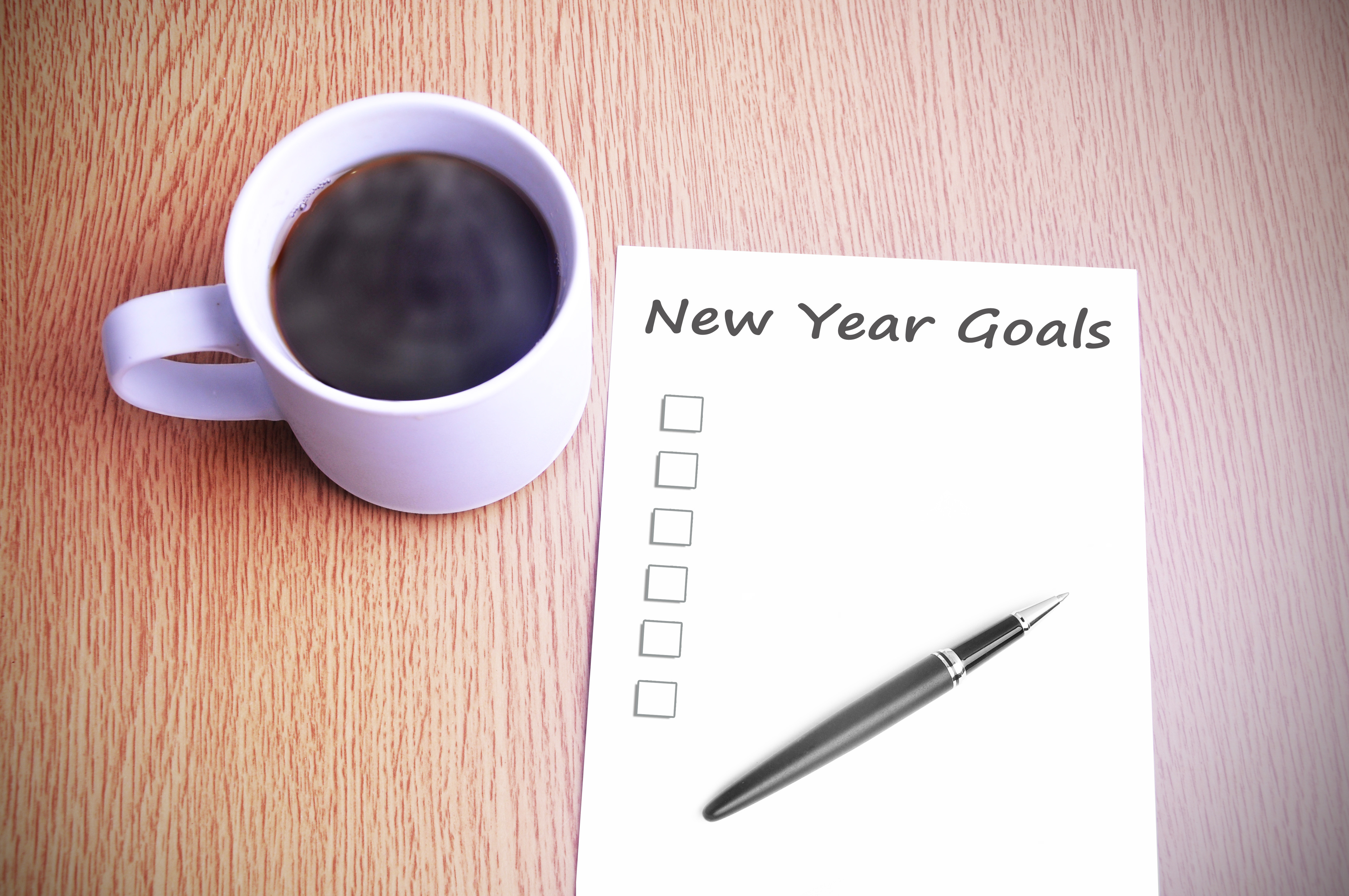 Coffee on the table with note writing new year goals