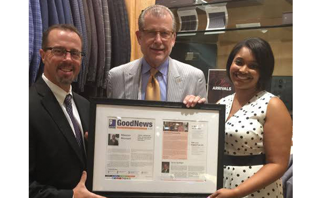 Representatives of Goodwill of Greater Washington present David Eisele, Sr. of Davelle Clothiers with a newsletter highlighting the business's contributions to Goodwill's mission