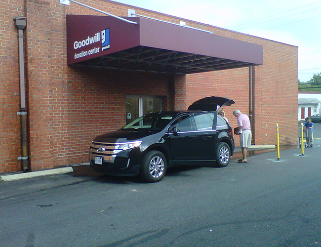 A black Ford edge at a Goodwill donation center in Rockville, MD with a man standing behind it donating goods