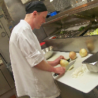 David Meloy, Marketing and Community Relations Manager, working as a lead cook (chopping onions) in a kitchen in 2012
