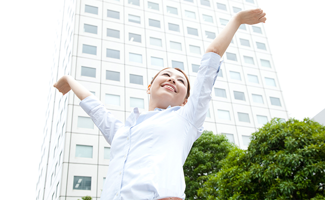 A woman in a white blouse stands in front of a building and tree with arms outstretched with a smile on her face