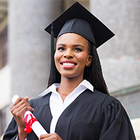 African American woman in a black graduation cap and gown with a rolled up diploma in her hand standing in front of a building with large pillars