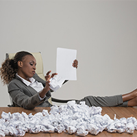 An African American woman in a gray business suit sits in a white desk chair with her feet up on a desk with crumpled up paper on it as she crumples up another piece of paper in one hand and holds a flat one in the other