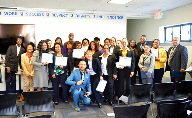 The first group of graduates from Goodwill of Greater Washington's hospitality program for the LINE hotel in Washington DC pose at their graduation with their diplomas