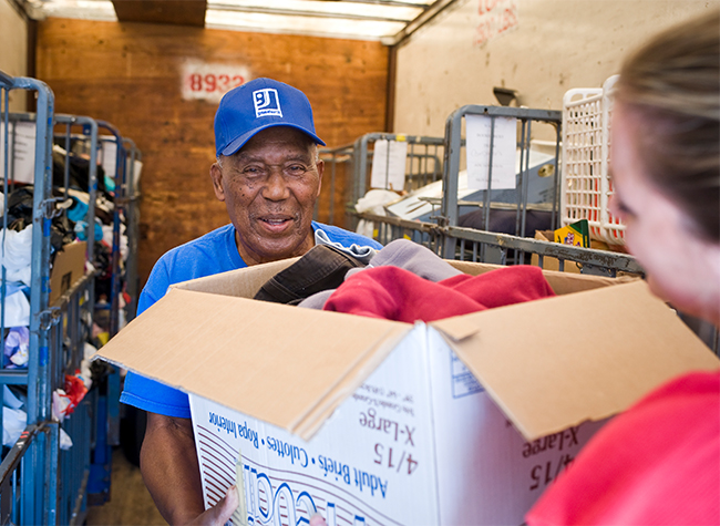 An African American man in a blue Goodwill hat accepts a box of donations from a woman in a pink shirt insided of a donation center