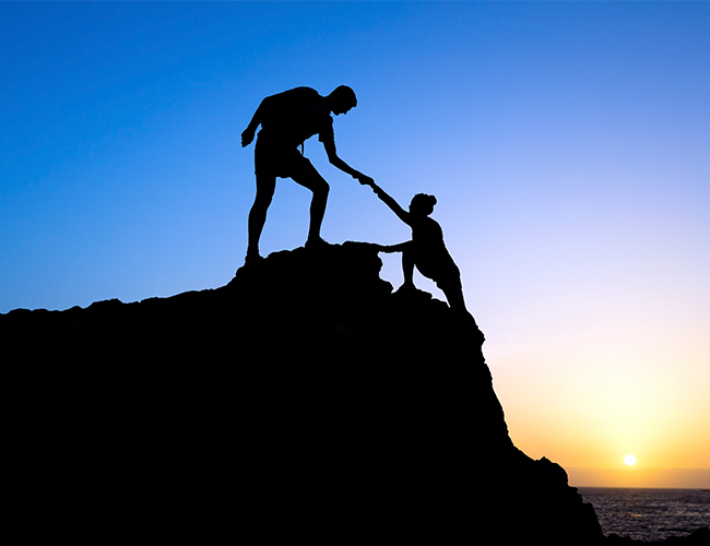Couple hiking help each other silhouette in mountains, sunset and ocean Male and woman hiker helping each other on top of mountain climbing, beautiful sunset landscape