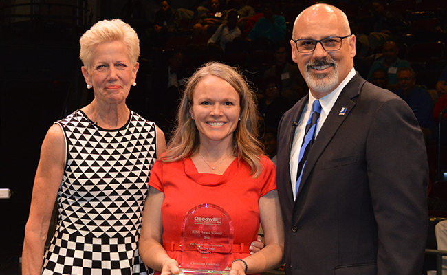 2017 Goodwill of Greater Washington RISE winner for Respect Christina Damhuis: Blonde woman in a red dress holding an award, with Catherine Meloy, Goodwill of Greater Washington CEO: woman in a black and white patterned dress, blonde, and Michael Frohm, Goodwill of Greater Washington COO, man in a business suit with a blue tie, bald with glasses