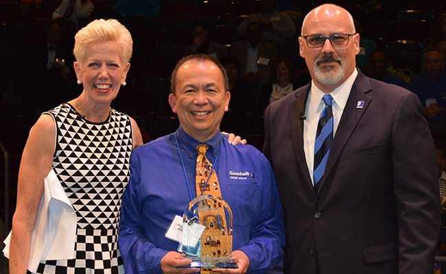 2017 Goodwill of Greater Washington RISE winner for Integrity Talby Afable: Man in a blue shirt and yellow tie holding an award, with Catherine Meloy, Goodwill of Greater Washington CEO: woman in a black and white patterned dress, blonde, and Michael Frohm, Goodwill of Greater Washington COO, man in a business suit with a blue tie, bald with glasses