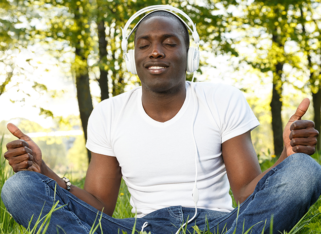 Stock Photo - Positive young african american man in white shirt listens to a podcast in a park