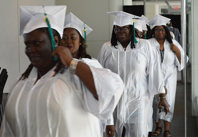A line of African American women in white caps and gowns walks into a room