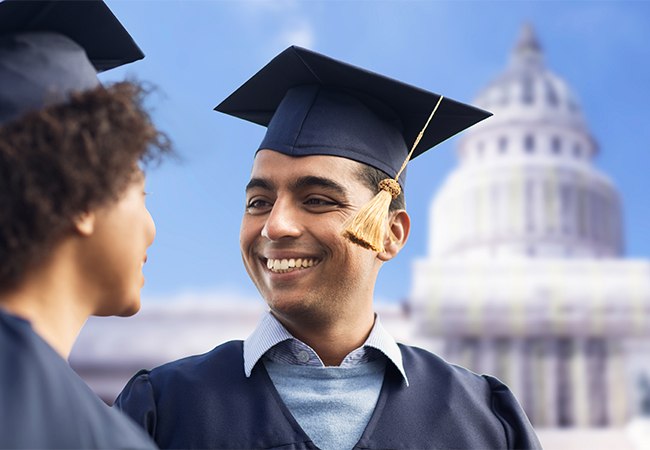 happy students or bachelors in mortar boards (an African American woman has her head turned away from the camera while a tan complected man faces her/the camera) in front of a blurred silhouette of the capital building in Washington D.C.
