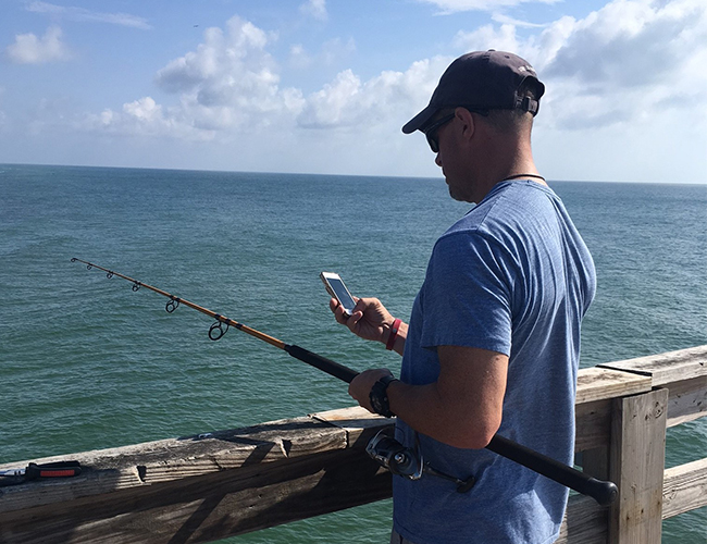 A man standing on a pier on a sunny day facing away from the camera toward the water. He has a fishing pole in one hand and is looking at a cell phone in the other. He has on a blue shirt, a blue hat, sunglasses, and khaki cargo shorts
