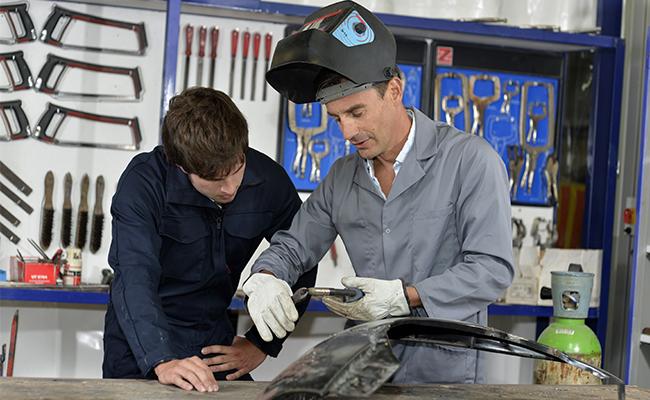 Trainee with instructor using welding machine