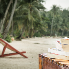 stack of books in foreground, island retreat in background