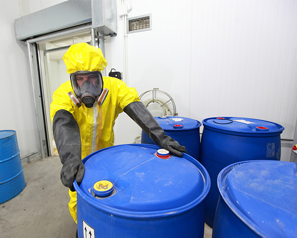 person wearing hazmat suit secures toxic waste barrel