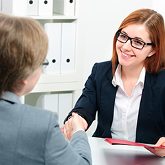 female interview candidate shakes interviewer's hand