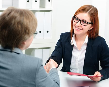 female interview candidate shakes hands with interviewer
