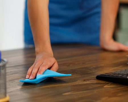 woman cleans a desk with a blue cloth