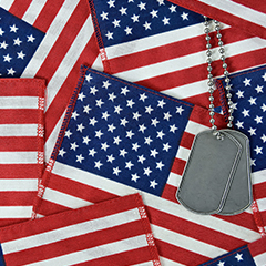 military dog tags laid over numerous american flags, memorial day flags