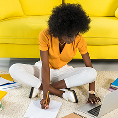 african american woman natural hair researches using laptop and pen and notepad