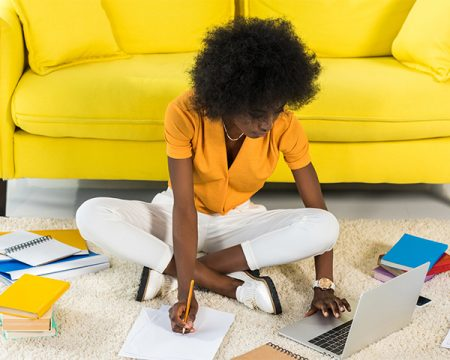 african america woman natural hair researches on laptop takes notes